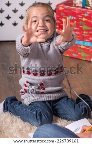 Full-length portrait of little cute fair-haired girl sitting on the floor near Christmas tree laughing and showing something her mother - stock photo