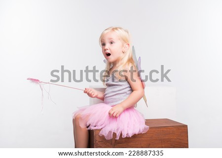 Full-length portrait of little fair-haired lovely girl wearing pretty grey vest pink skirt and white wings holding a magic wand sitting on the wooden chair looking at something very impressive.