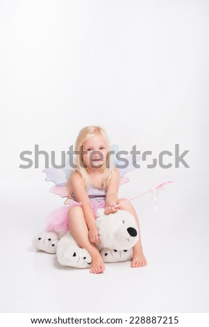Full-length portrait of little fair-haired lovely smiling girl wearing pretty grey vest and pink skirt sitting on the big teddy bear holding her magic wand. Isolated on white background - stock photo