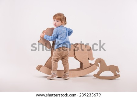 Full-length portrait of little lovely girl wearing blue shirt and brown pants standing back to us holding at the wooden toy horse. Isolated on the white background - stock photo