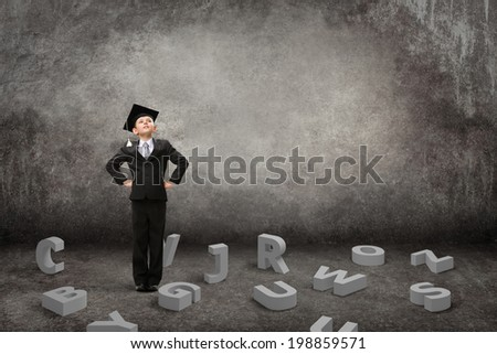 Full-length portrait of little student with hands on hips and letters under his feet on grey background. Concept of study and graduation - stock photo