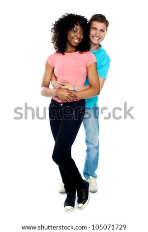 Full length portrait of love couple embracing against white background. Indoor shot - stock photo