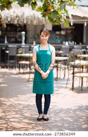 Full-length portrait of lovely Asian waitress of outdoor cafe - stock photo