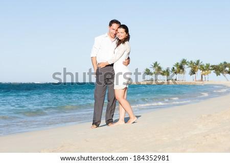 Full length portrait of loving couple embracing on beach - stock photo