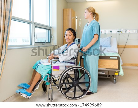 Full length portrait of male patient sitting on wheel chair with nurse standing behind at window in hospital