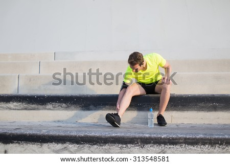 Full length portrait of male runner doing legs exercises for complete his daily fitness training outdoors,young sport man in fluorescent bright t-shirt warming up before begin his run in early morning - stock photo