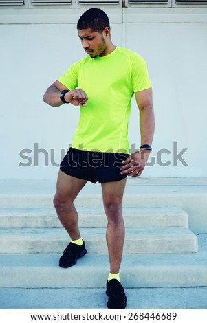 Full length portrait of male runner looking at his watch while going for a run at sunny afternoon,sporty young man dressed in bright t-shirt with space for your text message checking his time outdoors - stock photo