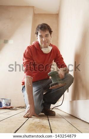 Full length portrait of man holding sander while kneeling in unrenovated room - stock photo
