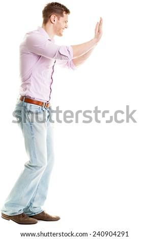 Full length portrait of man pushing something isolated on white background - stock photo