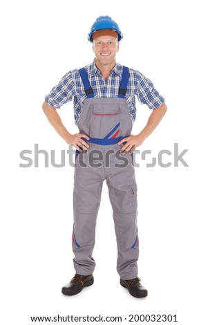 Full length portrait of manual worker standing with hands on hip over white background