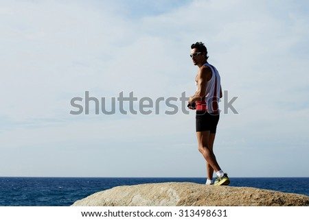 Full length portrait of mature male runner resting after active training on the beach while listening to music in headphones, sports man standing against sky background with copy space area for text - stock photo