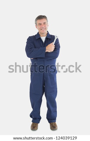 Full length portrait of mature mechanic with wrench standing against white background - stock photo