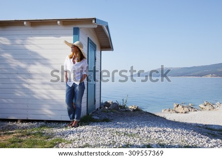 Full length portrait of middle age woman relaxing by the sea. Beautiful female standing near small vacation house while she is on holiday.  - stock photo