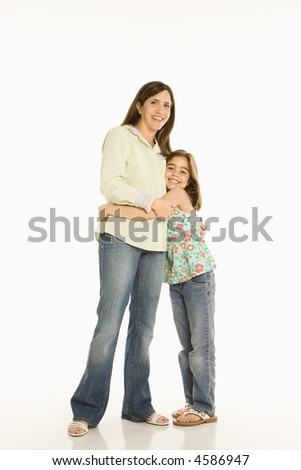 Full length portrait of mother and daughter standing hugging. - stock photo