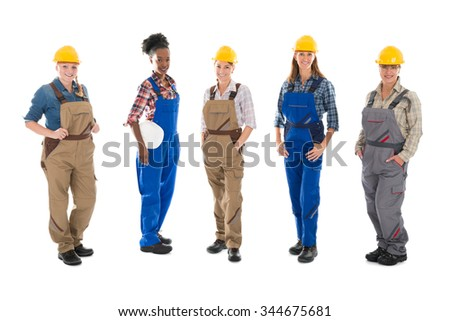 Full length portrait of multi ethnic female carpenters standing in row against white background