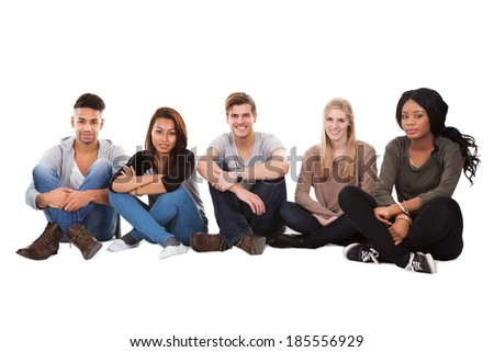 Full length portrait of multiethnic college students sitting in a row against white background - stock photo