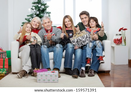 Full length portrait of multigeneration family with Christmas presents sitting on sofa at home - stock photo