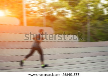 Full length portrait of muscular build sports man running along beautiful wall outdoors, male runner working out outside at amazing sunset light, filtered image, flare sunset light motion blur effect - stock photo