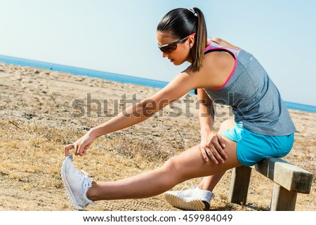 Full length portrait of muscular young female runner stretching hamstrings at beach front.