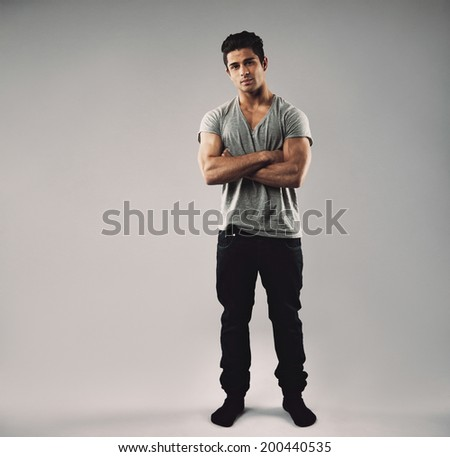 Full length portrait of muscular young man standing with his arms crossed. Hispanic mate model in casuals with copy space on grey background. - stock photo