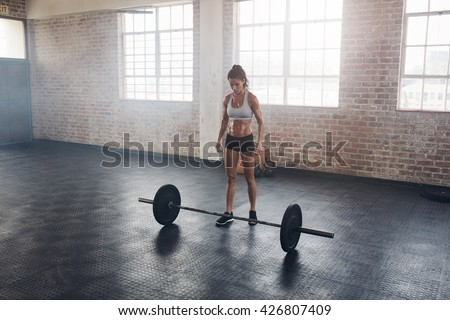 Full length portrait of muscular young woman standing at gym with barbells on floor. Strong female at gym. - stock photo