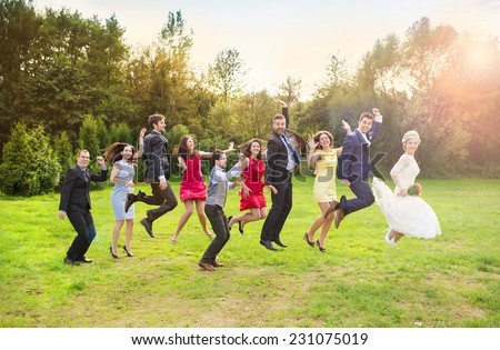 Full length portrait of newlywed couple with bridesmaids and groomsmen jumping in green sunny park - stock photo