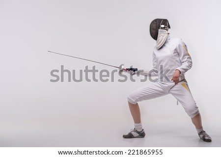 Full-length portrait of nice young woman wearing fencing costume and mask practicing before very important competitions. Isolated on white background - stock photo