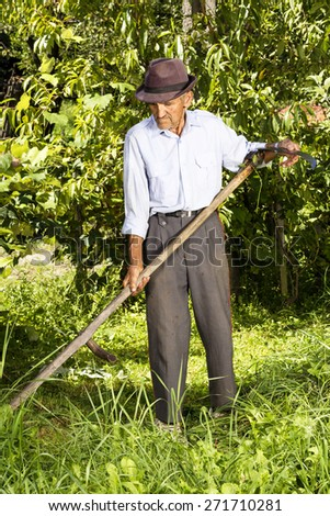 Full length portrait of old farmer preparing his scythe to mow the grass traditionally - stock photo