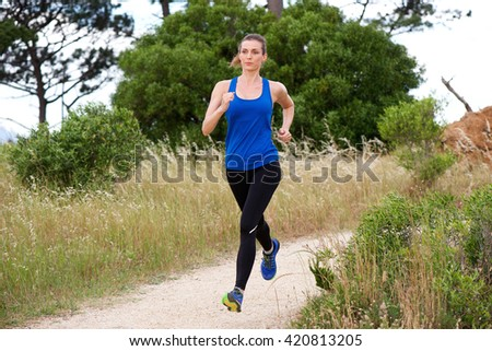 Full length portrait of older woman jogging in countryside