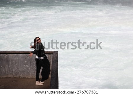 Full length portrait of one young adult woman stand in front of a waterfall Healthy lifestyle idea Cute girl relax and enjoy water splash move Female rest against wet mountain Hand up - stock photo