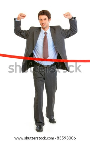 Full length portrait of pleased businessman  crossing finish line isolated on white. Concept - success achievement