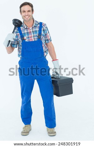 Full length portrait of plumber holding plunger and tool box over white background - stock photo