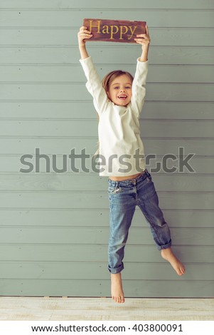 Full length portrait of pretty little girl holding a wooden plate, jumping and smiling, against gray background - stock photo