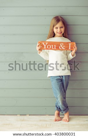 Full length portrait of pretty little girl holding a wooden plate, looking at camera and smiling, standing against gray background - stock photo
