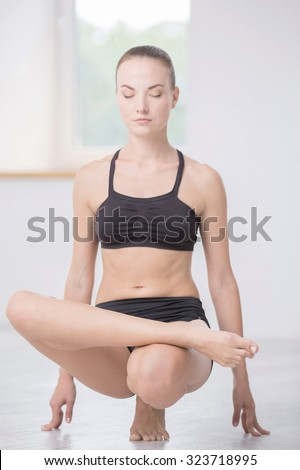 Full length portrait of pretty woman doing yoga exercises in gym - stock photo