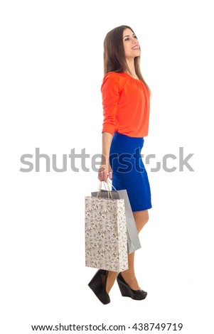 full length portrait of pretty young brunette with shopping bags in hands isolated on white background - stock photo