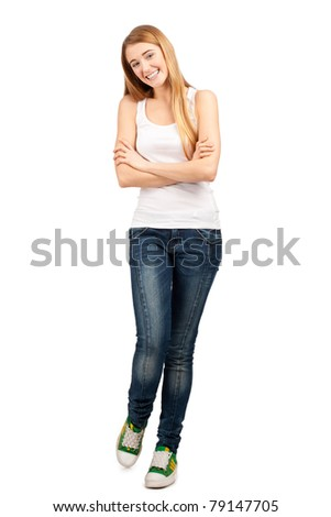 Full length portrait of pretty young woman standing with folded hands and smiling, against white background - stock photo