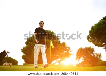 Full length portrait of professional golf player walking to the next hole on beautiful course, good golf game at sunny summer day on the course, bright flare sunset light - stock photo