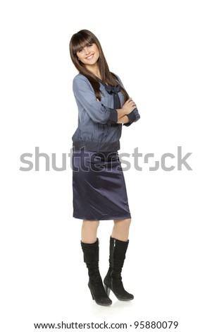 Full length portrait of relaxed young businesswoman standing with hands folded on white background - stock photo