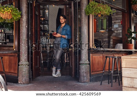 Full length portrait of relaxed young male standing at the entrance of a cafe and having coffee. Stylish young man at a cafe entrance door. - stock photo