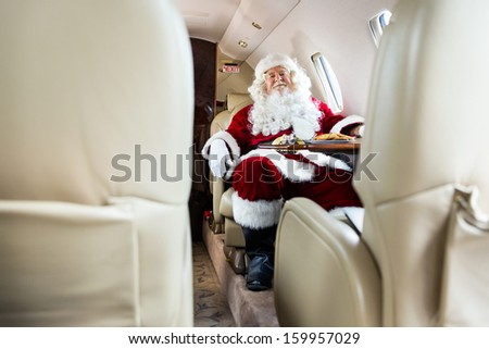 Full length portrait of Santa Claus relaxing in private jet - stock photo