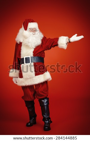 Full length portrait of Santa Claus showing something. Christmas time. Red background. - stock photo