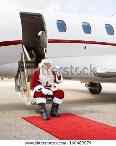 Full length portrait of Santa Claus toasting milk glass while sitting on private jet's ladder - stock photo