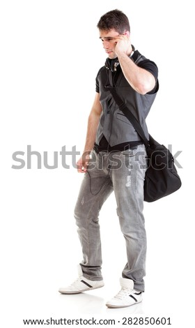 Full length portrait of school boy holding bag and talking on a phone isolated on white background - stock photo