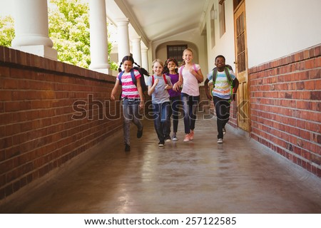 Full length portrait of school kids running in school corridor - stock photo
