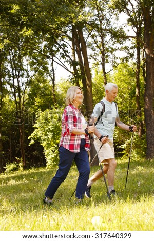 Full length portrait of senior couple nordic walking on the forest.  - stock photo