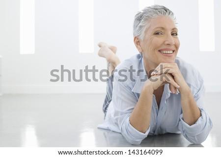 Full length portrait of senior woman lying on floor - stock photo