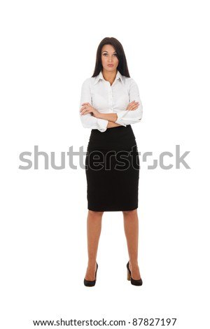 Full length portrait of serious business woman standing with folded hands in isolated over white background