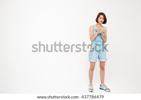 Full length portrait of serious pretty girl, in gray shirt and denim overall, making notes, isolated on white background - stock photo
