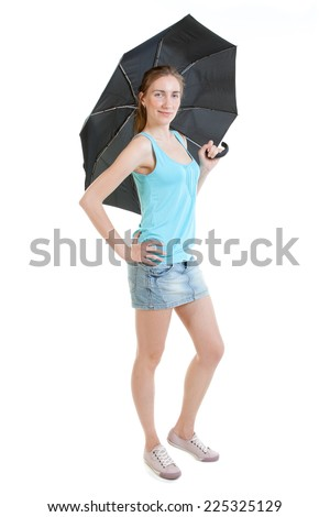Full-length portrait of sexy young woman wearing jeans mini-skirt, blue t-shirt and gumshoes with black umbrella - stock photo